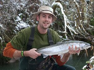 a man wearing waders holds a steelhead