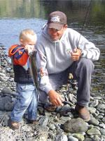 a father and young son stand on a pebbled shore. The son is holding up a trout.