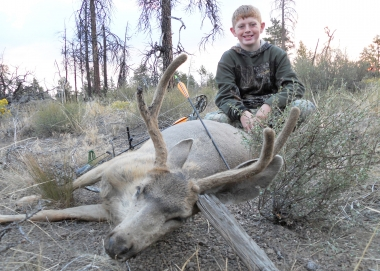 A young boy poses with a buck deer he shot with a bow and arrow