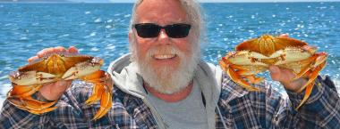 An older man with white hair and a white beard holds up two bright orange crab for the camera. The water behind the man is a bright blue.
