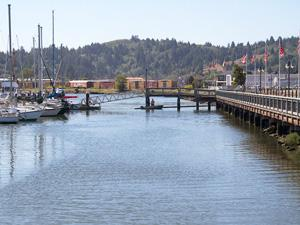 Coos Bay's boardwalk is on the right side of the image and a row of boats are tied to a dock on the left side of the image
