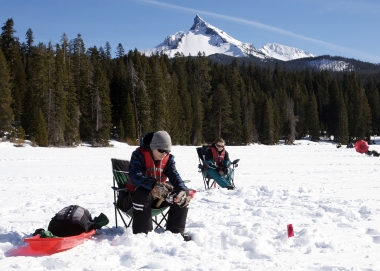Two anglers ice fishing at Diamond Lake in the shadow of Mt. Thielsen