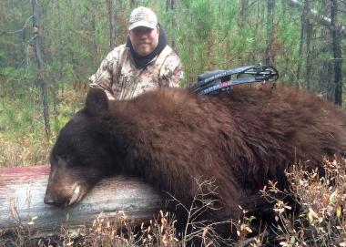 image of an archery hunter with large black bear