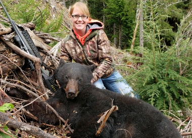 image of a young female rifle hunter with a bear