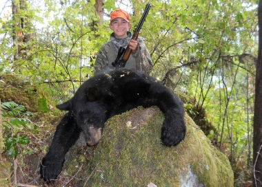 image of a young rifle hunter posing with a spring bear