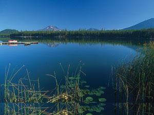 Big Lava Lake is a deep blue with tall grass and lilypads along its bank
