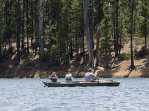 A man and two children fish from a small boat on South Twin Lake