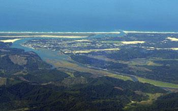 An aerial photo of the Siuslaw River flowing through Florence, OR.