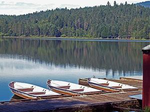 three row boats sit tied up to a dock on Lake Selmac
