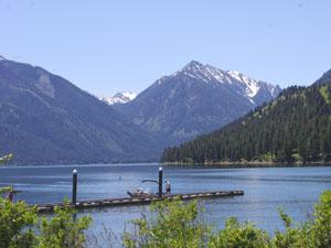 a dock extends into Wallowa Lake and mountains rise in the background
