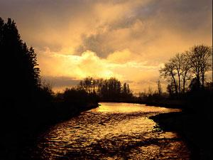 A yellow-orange sunrise illuminates a stretch of the Wallowa River.
