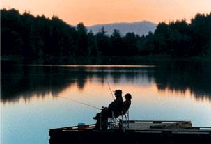 Two people sit in folding chairs on a deck that extends into Coffenbury Lake. The people are holding fishing rods and the sun is setting so that the sky is orange and the people are in silhouette