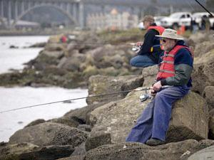 Two people sit on large boulders on the shore of Yaquina Bay with fishing lines in the water