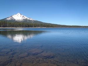 Fourmile Lake sprawls in the foreground with a snowy mountain in the background