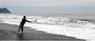 A woman stands barefoot on the beach and casts a long rod into the waves. She is fishing for surfperch.