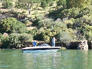 two people fish from a boat in Emigrant Lake