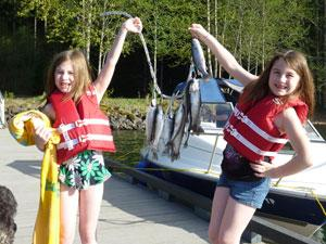 Two girls stand on a dock next to a boat. Each girl is holding up an end of a string of fish they presumably caught