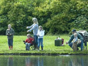 a family stands on the bank of Alton Baker Canoe Canal with fishing lines in the water and a cooler behind them