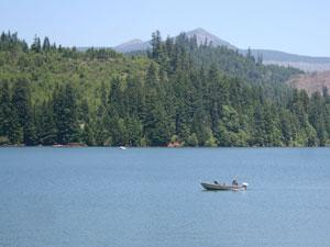 a small fishing boat sits in the middle of Foster Reservoir