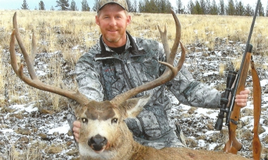 Hunter with massive mule deer