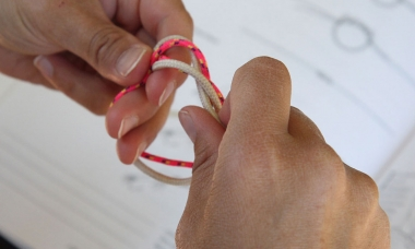 a person is practicing tying knots. A knot tying book is out of focus in the background