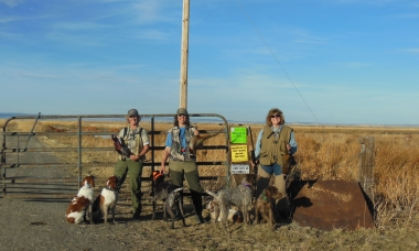 Three female hunters with their dogs, holding pheasants in front of access sign