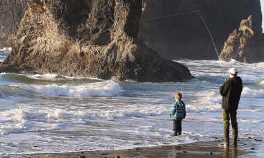 A photo of a man and young boy standing in the surf. The man has a fishing rod with the line cast out into the ocean.