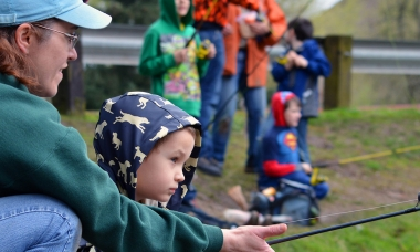 A mom helps her daughter hold a fishing pole at Canby Pond.