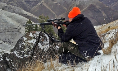 Rick Swart takes aim at an elk from his perch on the rim above Camp Creek in Northeast Oregon.