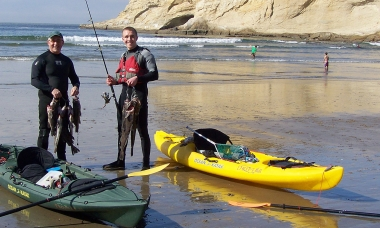 two kayak anglers on the ocean beach
