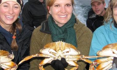 photo of three smiling women each holding a Dungeness crab