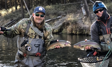 photo of two anglers, dressed for winter, each holding a nice trout