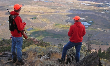 image of two deer hunters on a ridge scanning countryside