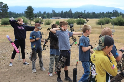 Kids practicing archery shooting in a line