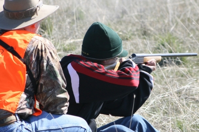image an adult coaching a young hunter on the shooting range