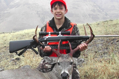 image of young hunter with his rifle and deer