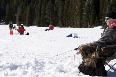 angler fishing through ice on Diamond lake