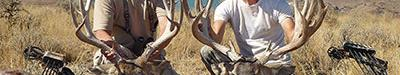two men pose with large buck deer they shot with bow and arrow